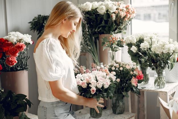 꽃과 꽃집. 여자는 꽃다발을 만든다.