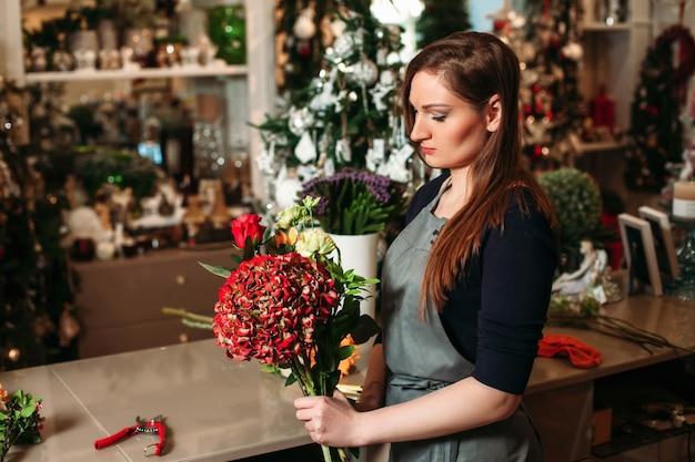 彼女の仕事を持つ花屋。