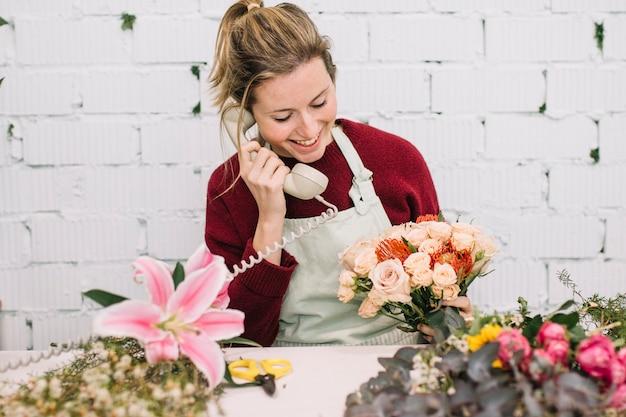 Флорист с приятным букетом разговаривает по телефону