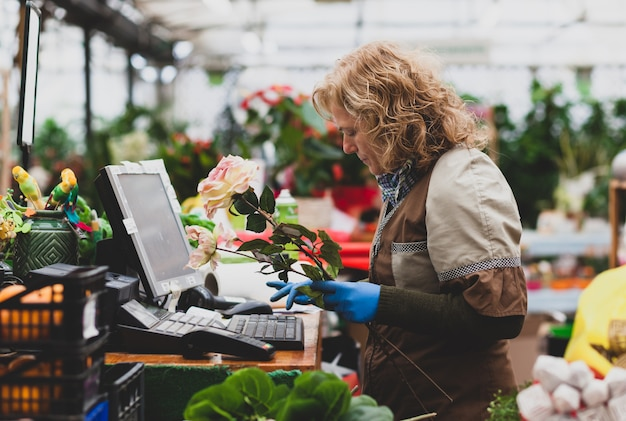 Florist with professional clothing in a shop