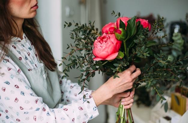 Женщина-флорист собирает букет розовых пионовидных роз, концепция малого бизнеса