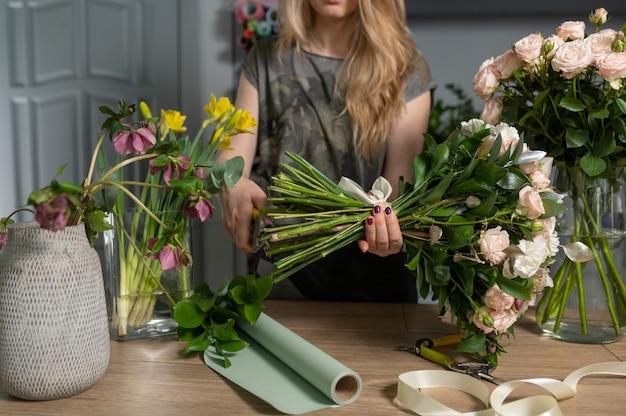 플로리스트 여자 꽃 꽃다발을 만듭니다.