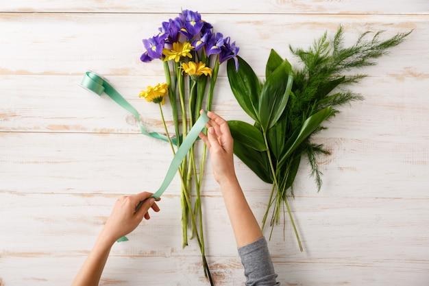 Флорист женщине руки, сделать букет из разноцветных цветов