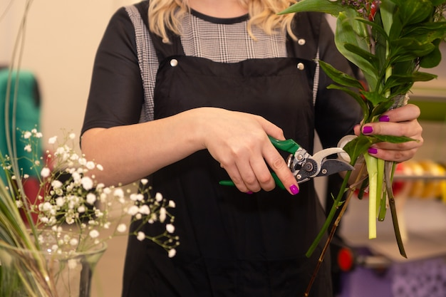 Florist woman hands making bouquet and cropping stems by pruner at flower shop