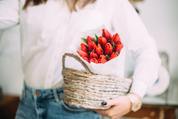 Florist woman holding a basket with red tulips in white paper. flower shop delivery concept