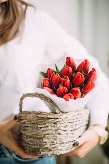 Florist woman holding a basket with red tulips in white paper.