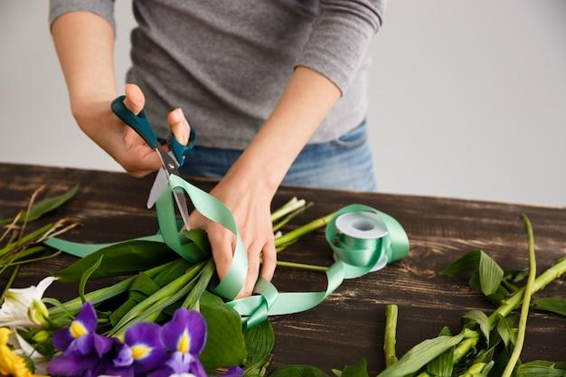 Флорист женщина делает букет, разрезает декорацию лентой