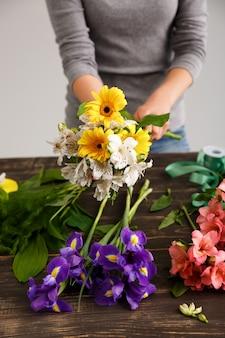 Флорист женщина делает букет из разноцветных цветов
