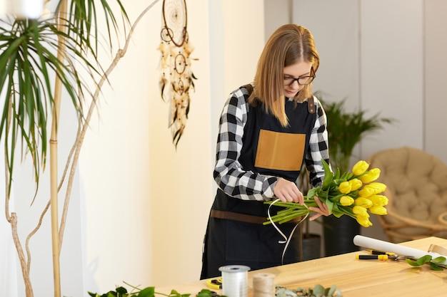 花屋の女性は新鮮な黄色いチューリップの花束を作ります。花の配達