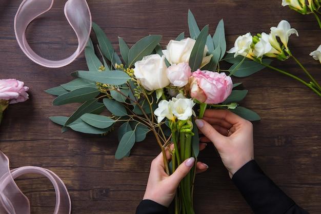 木製の背景にさまざまな花のファッションモダンな花束を作る花屋の女性
