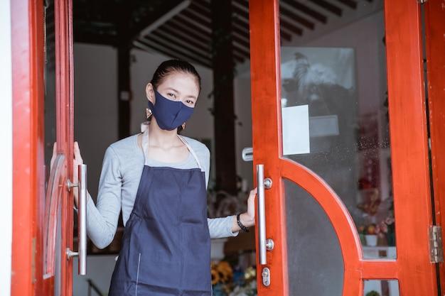 エプロンとフェイスマスクを身に着けている花屋の女性が立ってドアフラワーショップを開きます