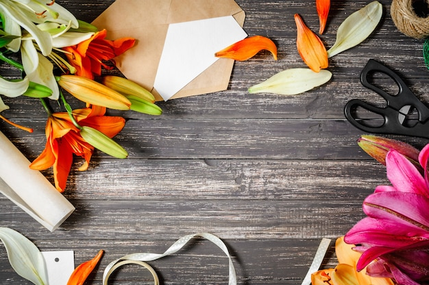 Florist work space with lilies flowers, scissors and kraft envelope flat lay background
