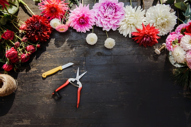 The florist work table with tools on dark wooden background. copy space