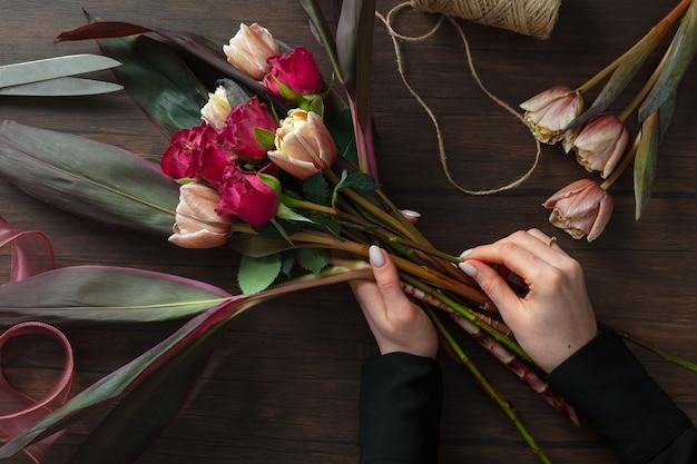 Fioraio al lavoro: donna che fa moda moderna bouquet di fiori diversi su fondo in legno. masterclass. regalo per la sposa per il matrimonio, la festa della mamma, la festa della donna. romantica moda primaverile. rose della passione.