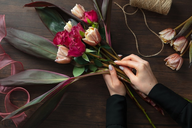 Florist at work: woman making fashion modern bouquet of different flowers on wooden surface.