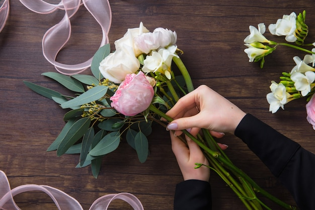 Florist at work: woman making fashion modern bouquet of different flowers on wooden table