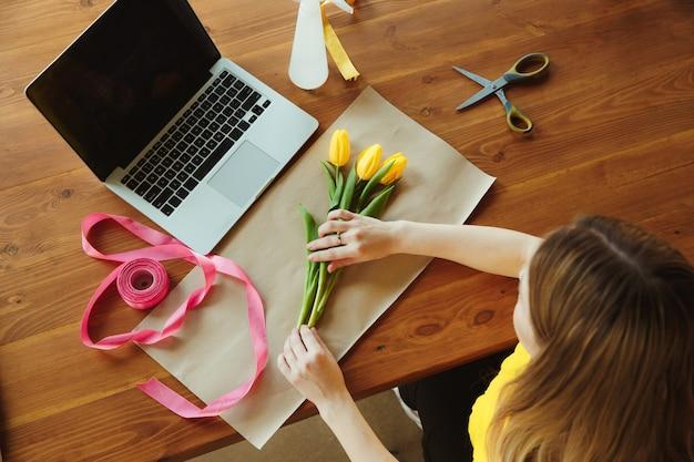 Fioraio al lavoro: la donna mostra come realizzare un bouquet con i tulipani. la giovane donna caucasica offre un seminario online per fare regali, regalo per la celebrazione. lavorare a casa mentre è isolato, in quarantena concetto.