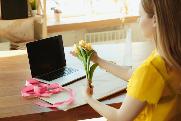 Florist at work: woman shows how to make bouquet with tulips.