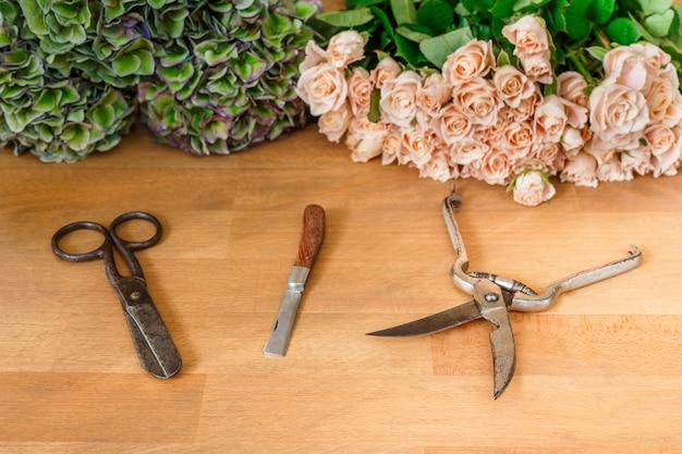 Инструменты и аксессуары для работы флориста, срезка свежих роз для букета в цветочном магазине. студия цветочного дизайна, изготовление декораций и композиций. доставка цветов, оформление заказа