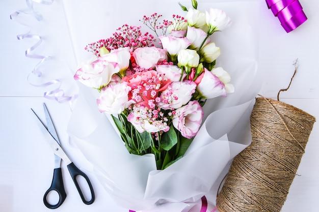 Флорист на рабочем месте, владелец бизнеса, флорист, создающий или оформляющий жилет из искусственных цветов в своем магазине, ремесле и концепции ручной работы. вид сверху, ножницы и веревка