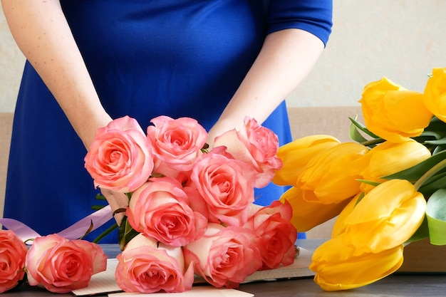 Florist workplace, florist makes a bouquet with roses