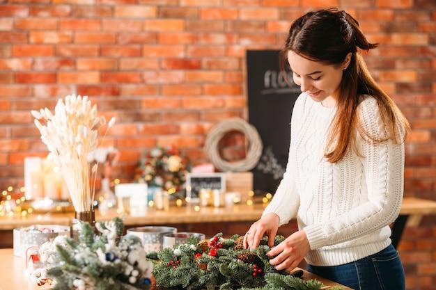 플로리스트 워크샵. 새로운 축제 겨울 장식 작업 크리 에이 티브 아가씨.