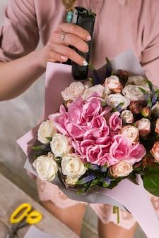バラの花の花束を包む花屋。デコレータはピンクの花束のある温室で動作します。フロリスティックワークショップ、スキル、装飾、中小企業のコンセプト
