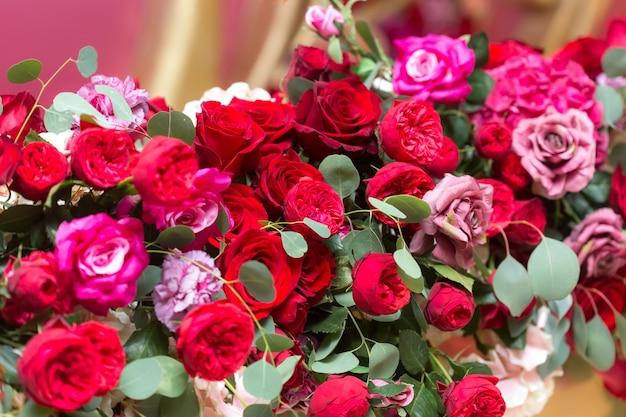 Флористическая композиция из великолепных красных пионовидных роз, гвоздик и веточек эвкалипта.