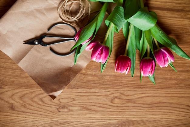 Флористическое рабочее место с крафт-бумагой, шпагатом. организация букета розовых тюльпанов на деревянном столе, хобби, поделки, концепция весеннего подарка, сверху.