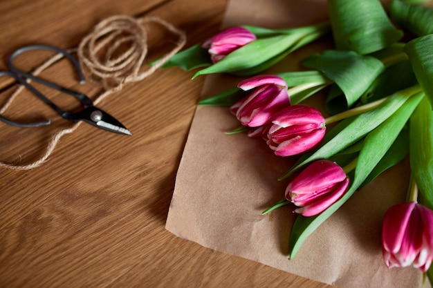 Floristic workplace with craft paper, twine arranging pink tulips bouquet on wooden table, hobby, diy, spring gift concept, from above.