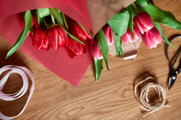 Floristic workplace with craft paper, twine arranging red tulips bouquet on wooden table, hobby, diy, spring gift concept, from above.
