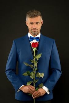 儀式のための植物相タキシードのボウタイの赤いバラのシンボルの結婚式のハンサムな男の豊富な新郎
