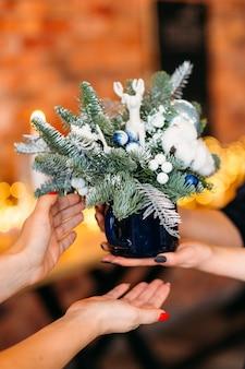 꽃집 선물 가게 배달 서비스. 머그잔에 하얀 가짜 눈, 사슴, 목화 식물 전나무 나무 배열의 근접 촬영.