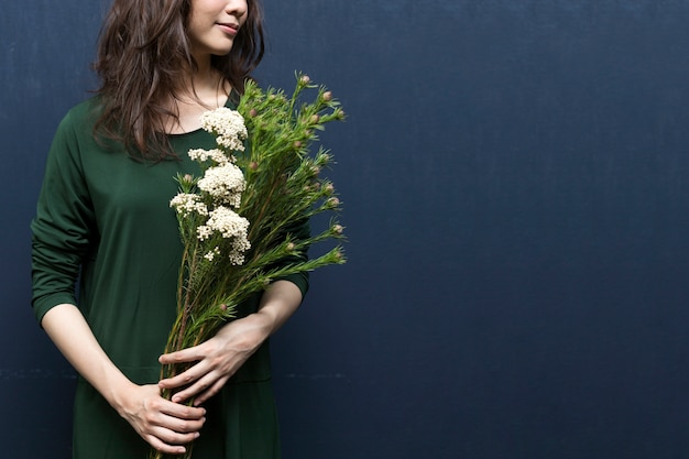 Floristry concept - close up of florist woman holding flower with space