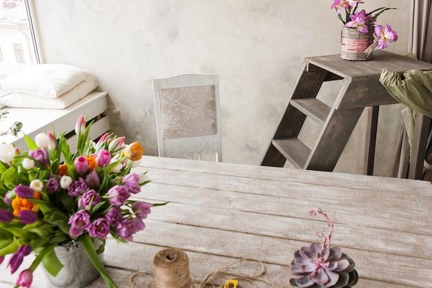 Предпосылка рабочего места флористики. красочные цветы, инструменты в белом интерьере. флорист, декоратор, сделай сам, мастерство, концепция весеннего подарка