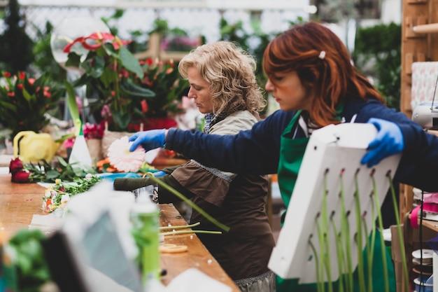 Florists work in a nursery.