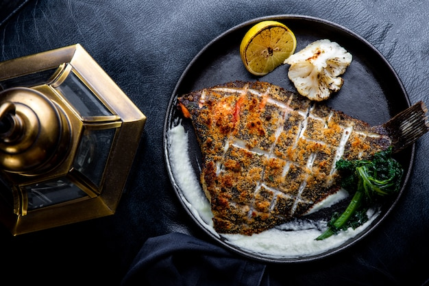 Flounder fillet roasted in a skillet with herbs and lemon