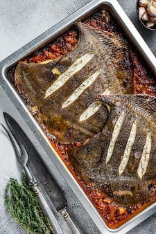 Flounder flat fish roasted in a tomato sauce in baking tray. white background. top view.
