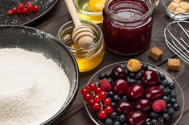 Мука и ягоды. баночка с медом и вареньем. ингредиенты для запекания ягодного пирога. темная деревянная поверхность. вид сверху