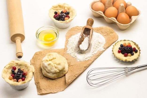 Бумага, мука, тесто. чашка для выпечки с замороженными ягодами и тестом. венчик, лоток для яиц и желток в миске. лоток для яиц.