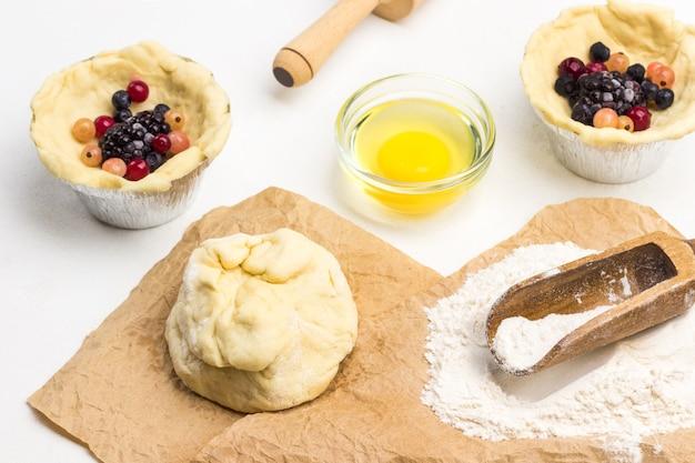 Бумага, мука, тесто. замороженные ягоды и тесто в чашке для выпечки. белый фон. вид сверху