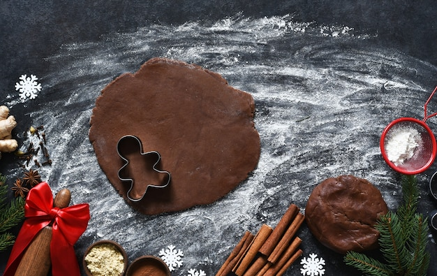 Мука и тесто скалкой на кухонном столе. ингредиенты для изготовления пряничного человечка. вид сверху