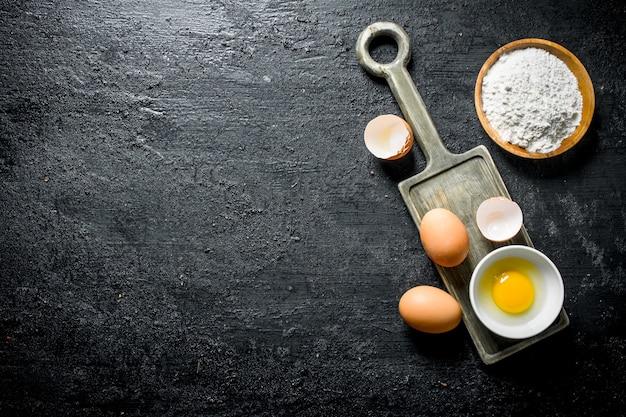 검은 시골 풍 테이블에 밀가루와 신선한 계란