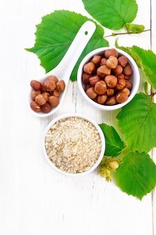 2つのボウルに小麦粉とヘーゼルナッツ、皮をむいたクルミの穀粒が入ったスプーン、上から木の板の背景に緑の葉が付いたヘーゼルナッツの枝