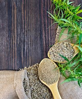 Семена муки и конопли в ложке, зеленые веточки конопли на фоне мешковины на темной деревянной доске