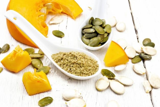スプーンで小麦粉とカボチャの種、明るい木の板の背景に野菜のスライス