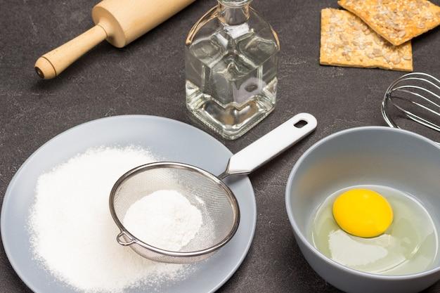 灰色のプレートに小麦粉とふるいをかけます。ボウルに卵黄。テーブルの上に水とクッキーでデカンター。調理。黒の背景。上面図