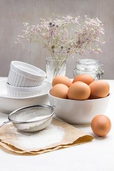 종이에 밀가루와 체. 계란이 탁자 위에 있어요. 그릇에 갈색 닭고기 달걀입니다. 화이트 세라믹 요리.