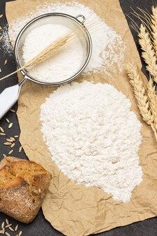 小麦粉と紙に小麦粉をふるいにかける。パンと小麦の小穂。フラットレイ。