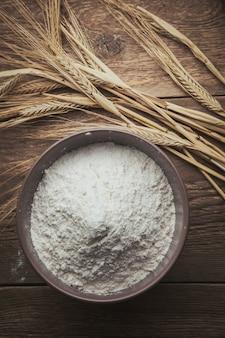 Мука и пшеница плоско лежат на деревянном